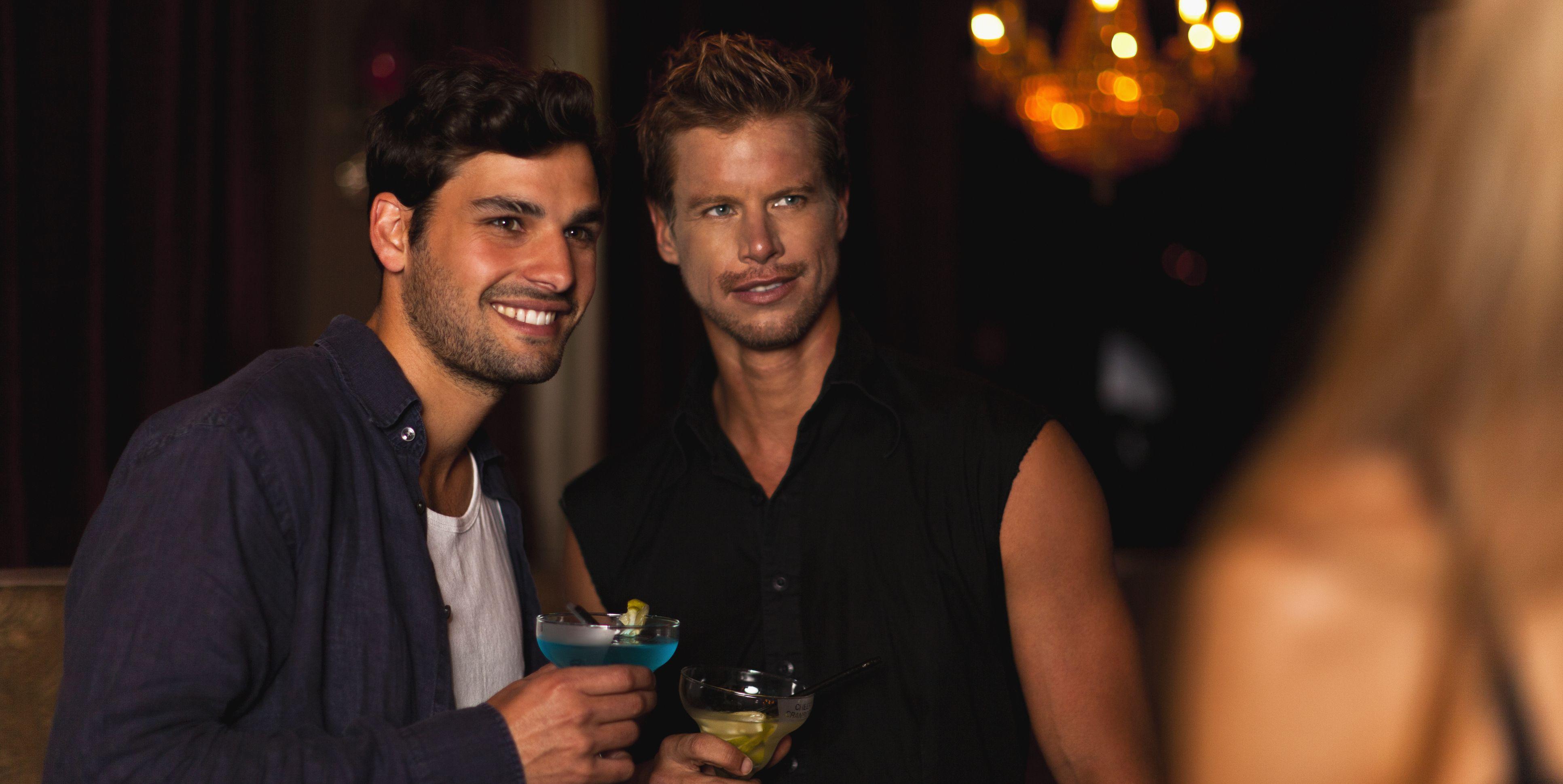 Smiling men having cocktails in club