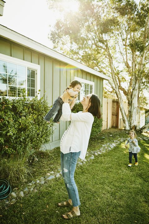 smiling mother holding infant son in air in front yard of home on summer morning