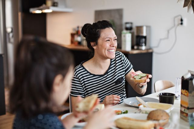 smiling mother sitting with daughter while having breakfast at dining table