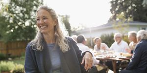 Smiling senior woman enjoying garden party lunch with friends on sunny patio