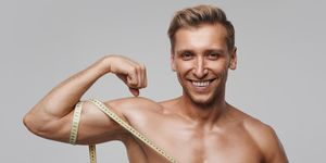 Smiling sportive man measuring bicep