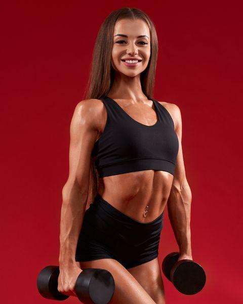 smiling sportsswoman holding dumbbells