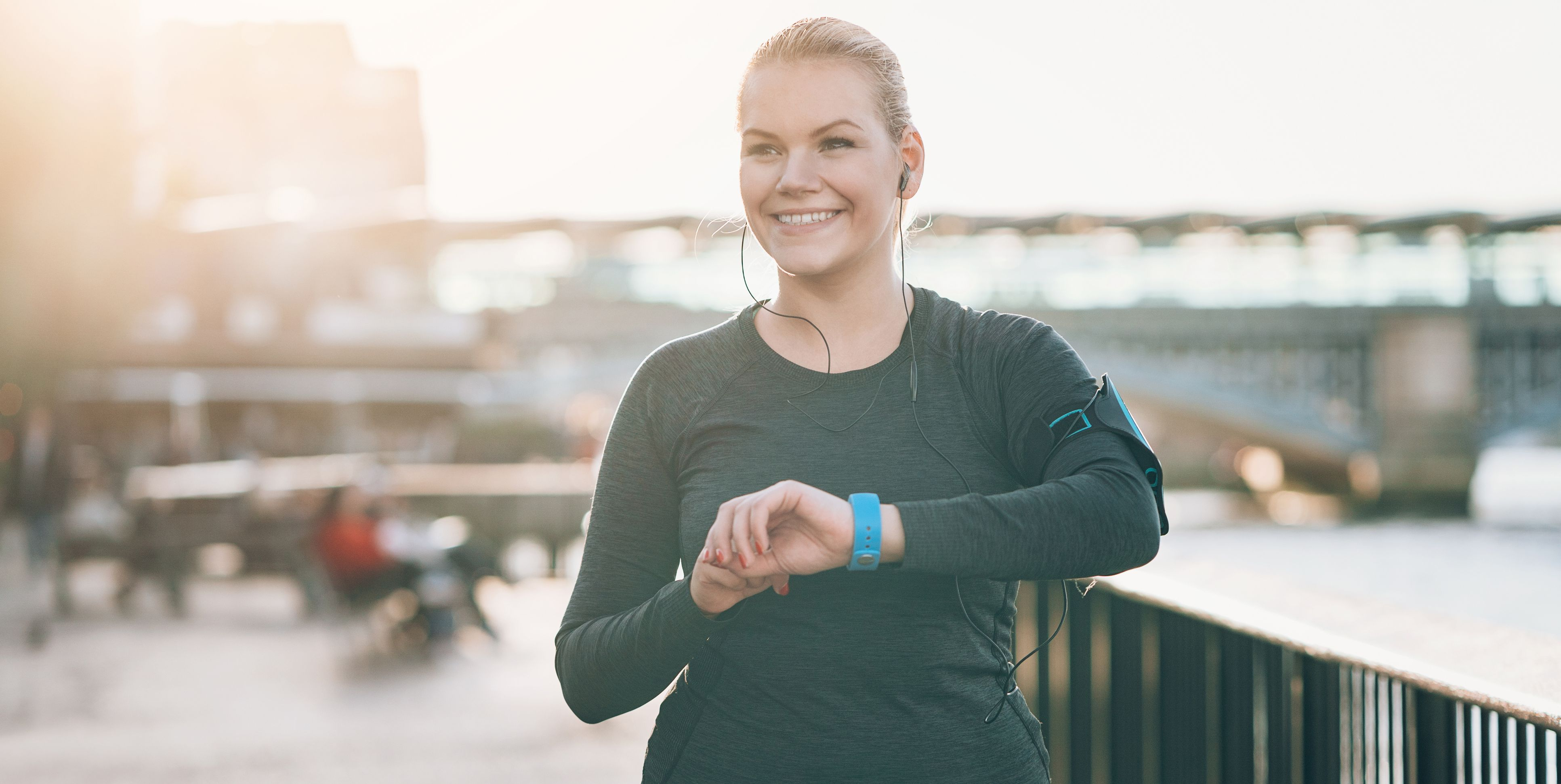 Smiling sportswoman checking her smart watch
