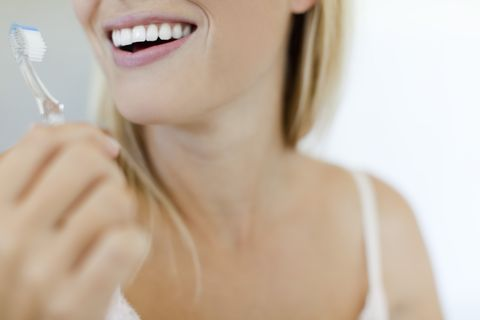 smiling woman brushing teeth, cropped