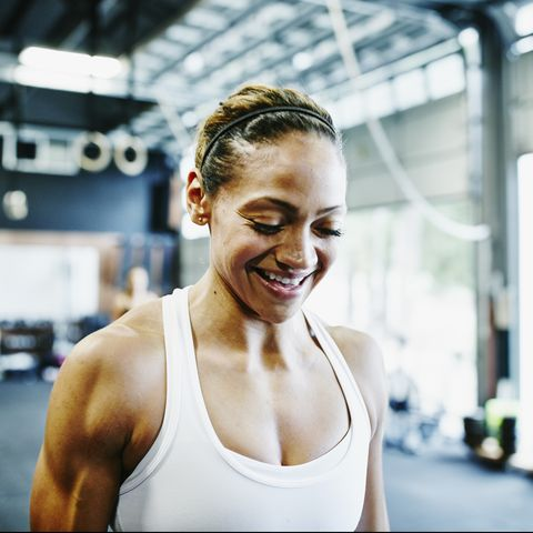 Smiling woman carrying kettlebells during workout