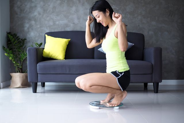 smiling woman crouching on weight scale at home