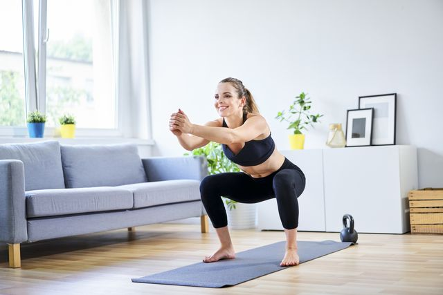 smiling woman doing squats during home workout