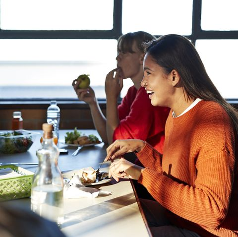 smiling woman enjoying lunch with friend at table