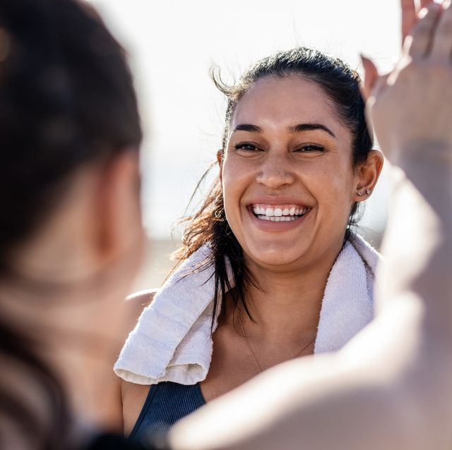 smiling woman giving high five to her friend after exercising