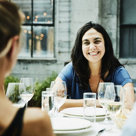 Smiling woman hanging out with friends during dinner on restaurant patio