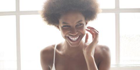 Smiling woman in bra standing by window
