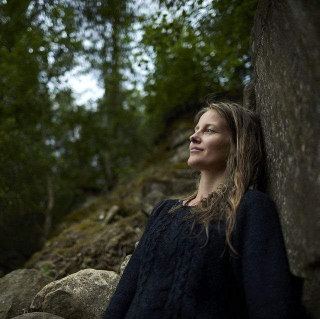 Smiling woman leaning against a rock in nature