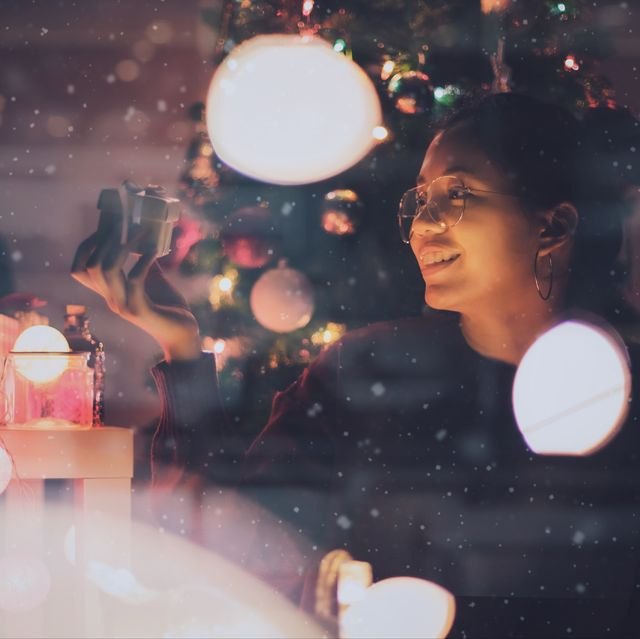 Smiling Woman Looking At Christmas Present Seen Through Glass Window At Night