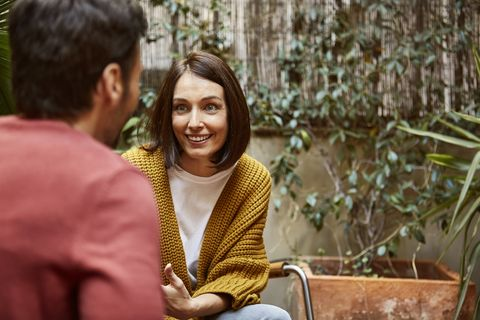 smiling woman looking at man in yard