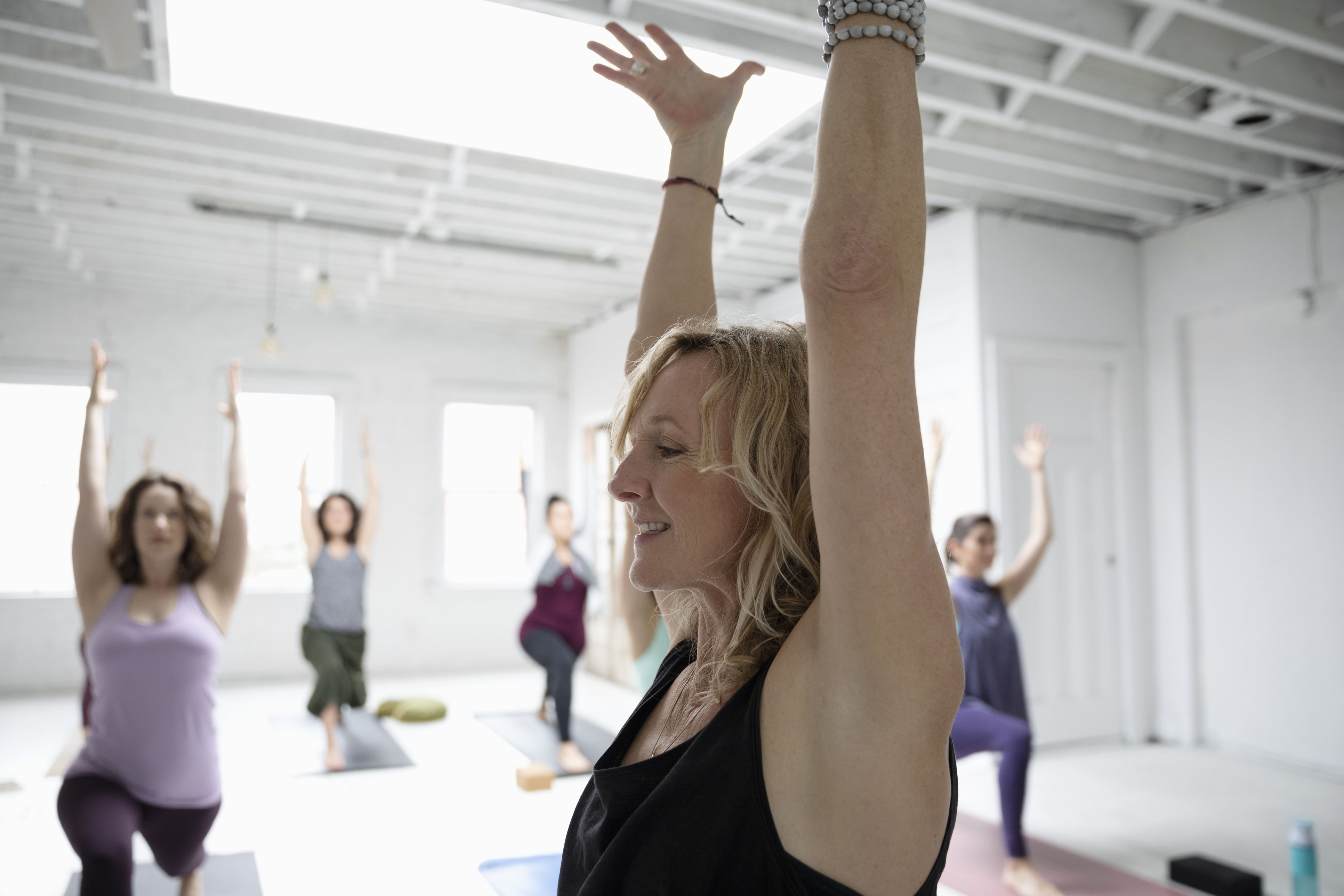 Smiling woman practicing yoga warrior one pose in yoga class