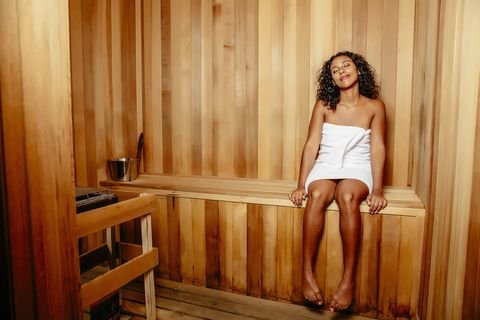 Smiling woman relaxing in sauna