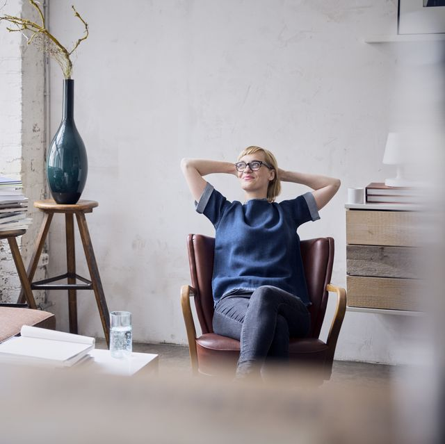 smiling woman sitting on arm chair in loft looking through window