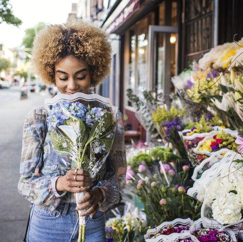 smiling woman smelling hydrangeas outside flower shop