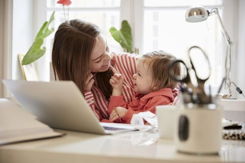 Smiling woman talking to daughter while working on laptop at home