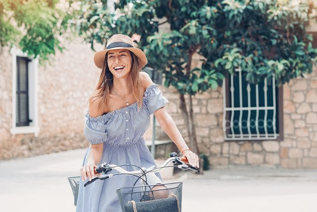 smiling woman with bicycle on a town street