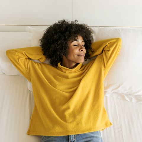 Smiling woman with closed eyes lying on bed