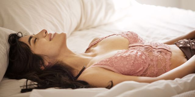 smiling woman with eyes closed lying on bed at home