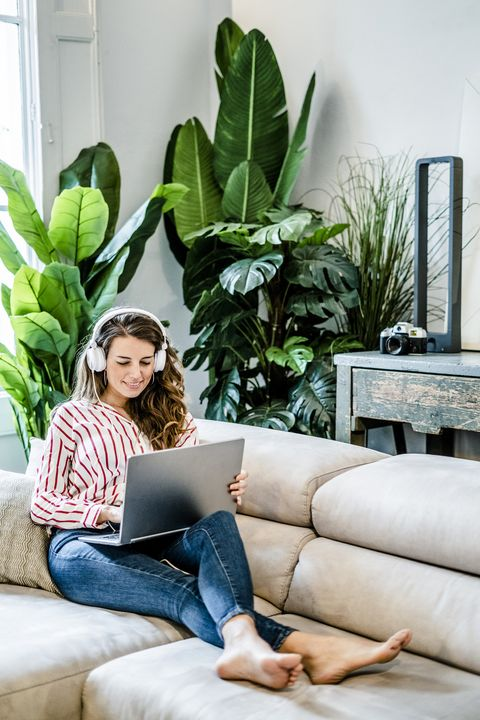smiling woman with laptop and headphones sitting on couch