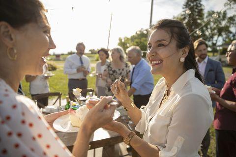 Smiling women eating cake, celebrating at sunny rural garden party
