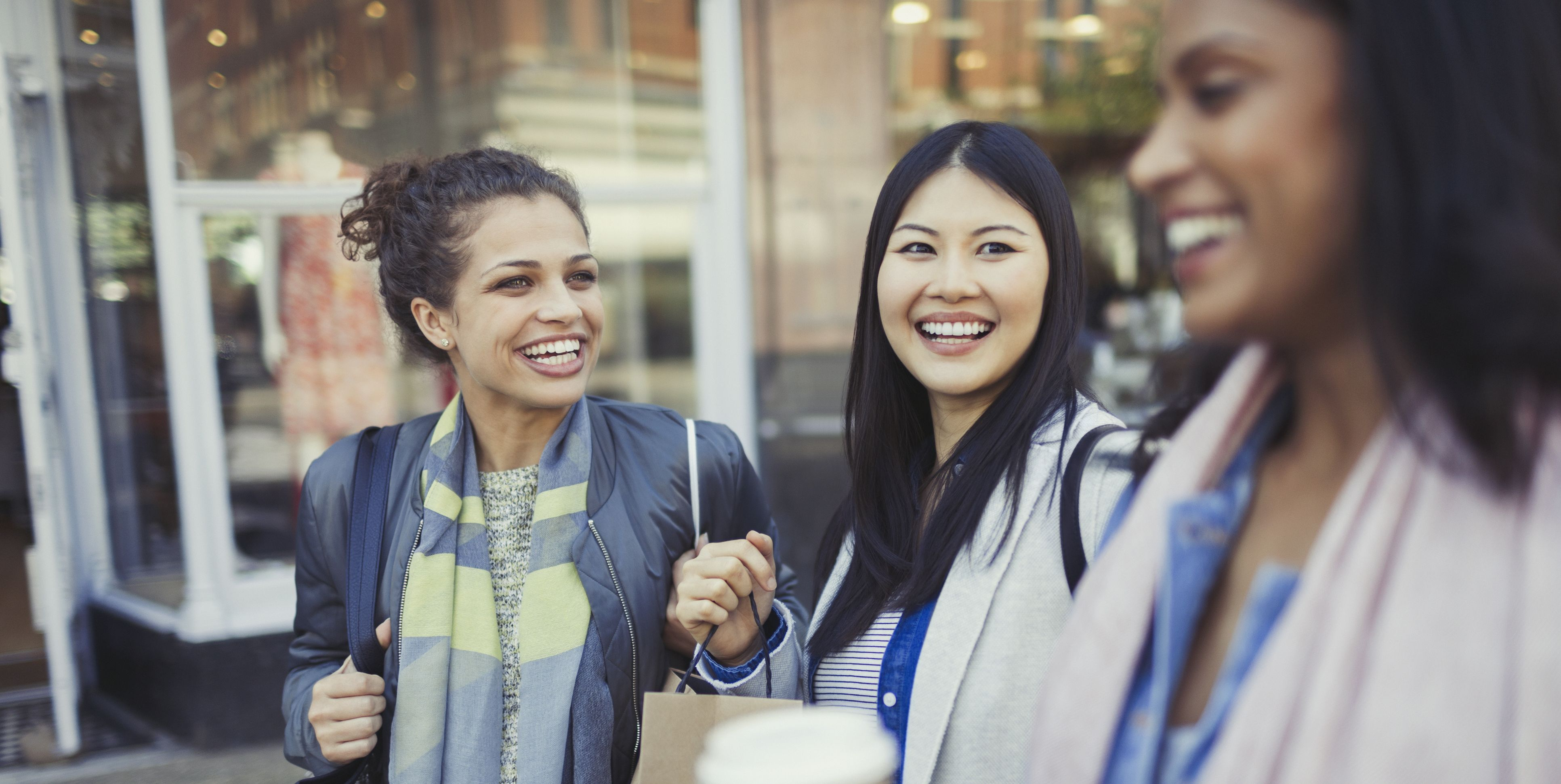 Smiling women friends with shopping bags and coffee outside storefront