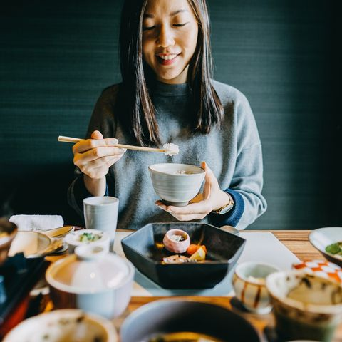 smiling young asian woman enjoying delicate japanese style cuisine with various side dishes, seafood and green tea in restaurant
