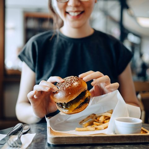 smiling young asian woman enjoying freshly made delicious burger with fries and a glass of iced coffee in a cafe