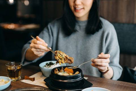 Smiling young Asian woman enjoying Korean meal in a Korean restaurant