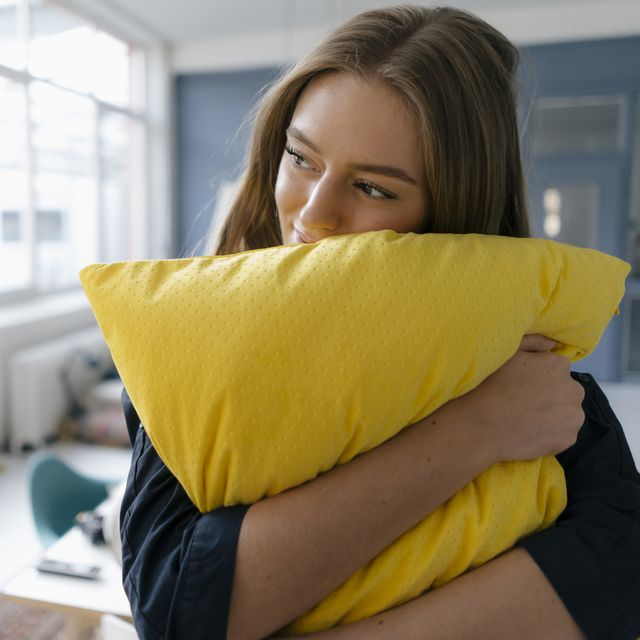Smiling young businesswoman with yellow pillow in office