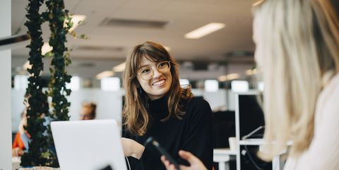 Smiling young female colleague sitting at desk in office