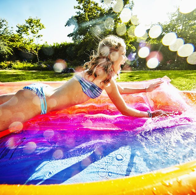 Smiling young girl splashing into pool
