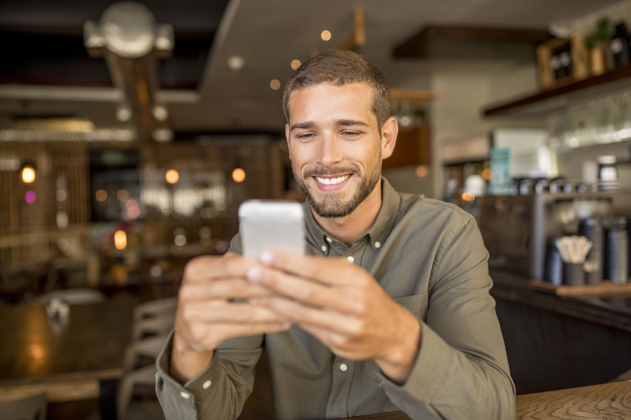 Smiling young man using smartphone in a cafe