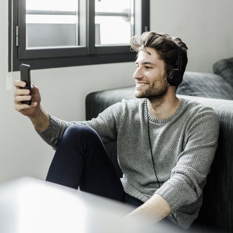 Smiling young man with cell phone and headphones at home