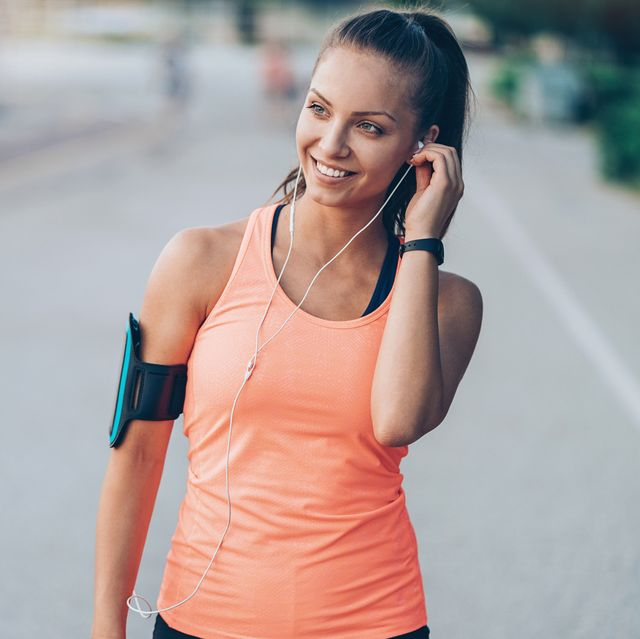 Smiling young sportswoman with arm band and headphones