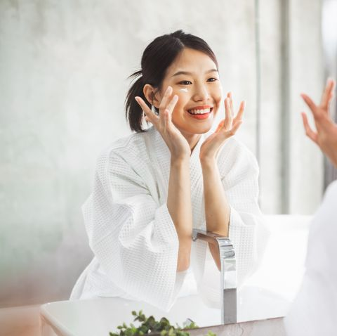 smiling young woman applying moisturizer on face on mirror in bathroom