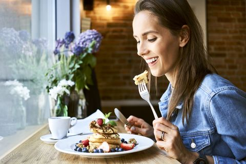 Smiling young woman eating pancakes in cafe