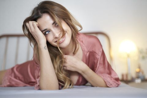 smiling young woman in dressing gown lying in bed looking sideways