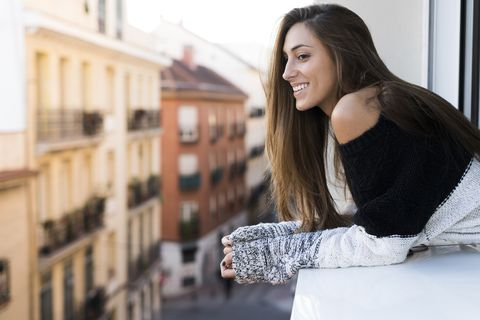 Smiling young woman leaning on window sill
