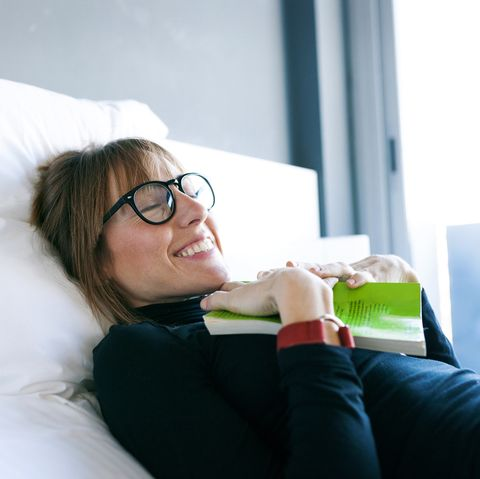 Smiling young woman lying on bed with book