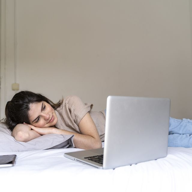Smiling young woman lying on bed with smartphone and laptop