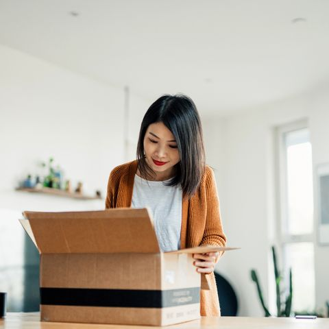 smiling young woman opening a delivery box in the living room