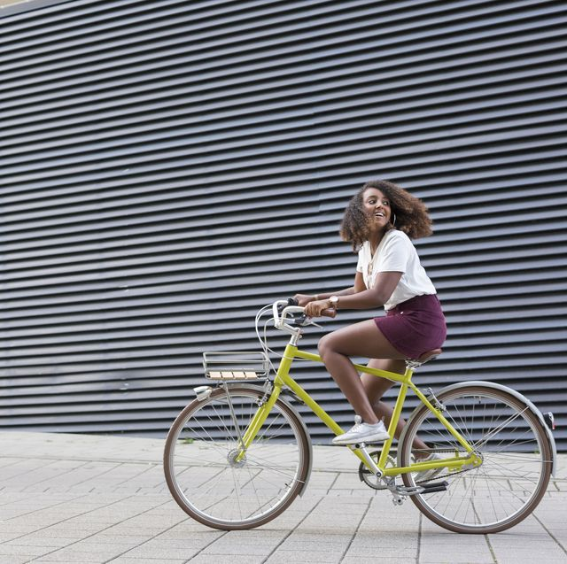 smiling young woman riding bicycle