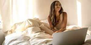 Smiling young woman with laptop in bed