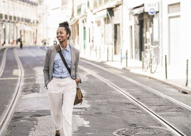 smiling young woman with wireless earphones in the city on the go, lissabon, portugal