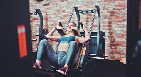 smilling sportswoman doing squatting in training machine at gym leg muscle training