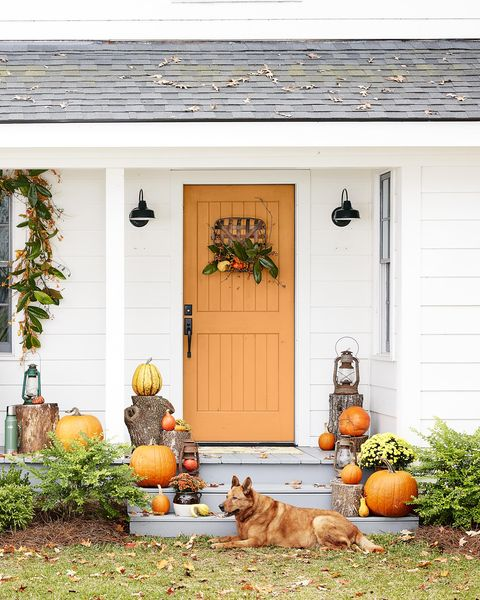 fall decorated porch with a magnolia garland over the window and a tobacco basket  wreath on the door